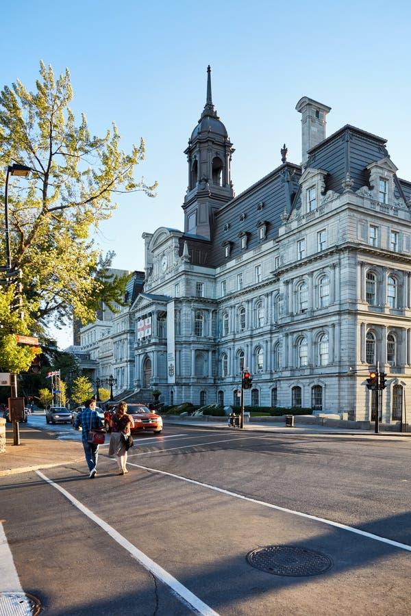 Ayuntamiento de Montreal L 'hotel de ville y un par canadiense que cruza la calle en una tarde soleada del verano en Montreal, Qu foto de archivo