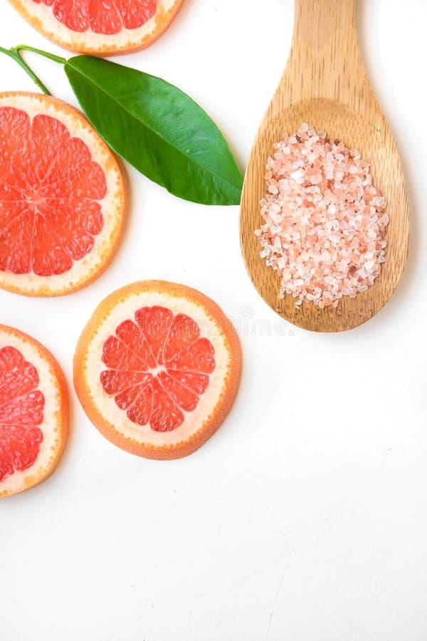 Ayurveda affronta la pelle sfrega gli ingredienti, sale himalayano di rosa in cucchiaio di legno, pompelmo affettato, foglia verd immagini stock libere da diritti