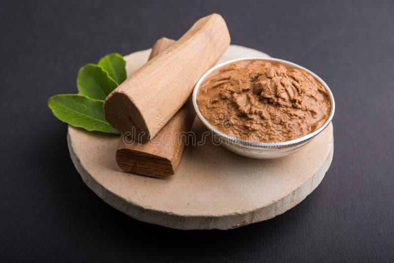 Ayurvedic chandan lape or lep or sandalwood paste. Ayurvedic Chandan powder or sandalwood paste in silver bowl with sticks and leaves placed over sahan or sahana stock photo