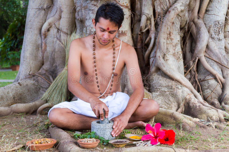 Ayurvedic Doctor. A young man preparing ayurvedic medicine in the traditional manner in India royalty free stock photos