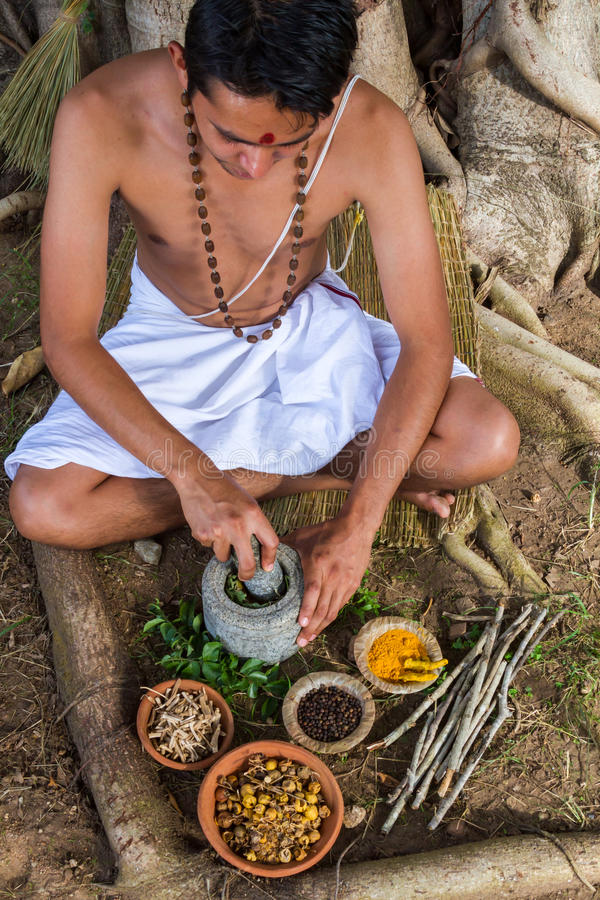 Ayurvedic Doctor. A young man preparing ayurvedic medicine in the traditional manner in India stock images