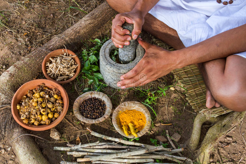 Ayurvedic Doctor. A young man preparing ayurvedic medicine in the traditional manner in India royalty free stock photo