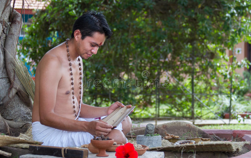 Ayurvedic Doctor. A young ayurvedic doctor reads ancient vedic palm leaf scrolls in the traditional manner in India royalty free stock image