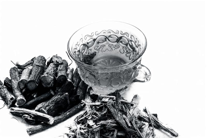 Famous herb Licorice root or Liquorice root or Mulethi root isolated on white along with its tea in a transparent cup. stock images