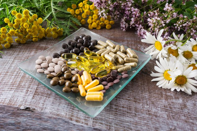 Ayurvedic herbal pills as healthy life concept. Ayurvedic herbal pills on the glass plate and wild chamomile, tansy, oregano. Healthy life concept royalty free stock photography