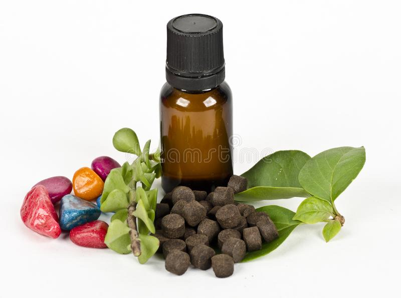 Ayurvedic medicine pills with herbs and oil. On white background stock image
