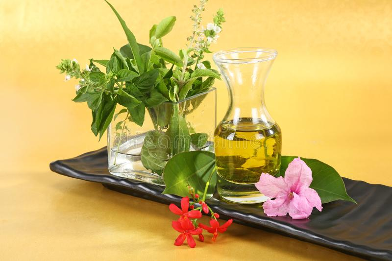 Ayurvedic Oil or Herbal Hair Oil with Herbs. On Yellow Background royalty free stock photos