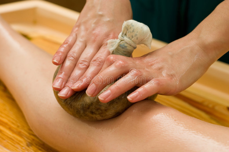Ayurvedic oil massage. Ayurvedic therapy: massage procedure with oil and pouch of rice and spices stock photos