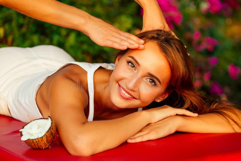 Ayurvedic relaxing massage ,health beauty happy closed eyes woman in spa salon getting massage on the holiday beach royalty free stock photography