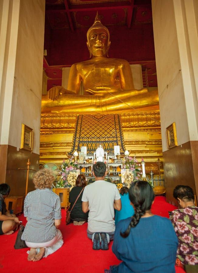 AYUTHAYA,泰国- 2013年11月22日:崇拜者在stat附近祈祷 免版税库存照片