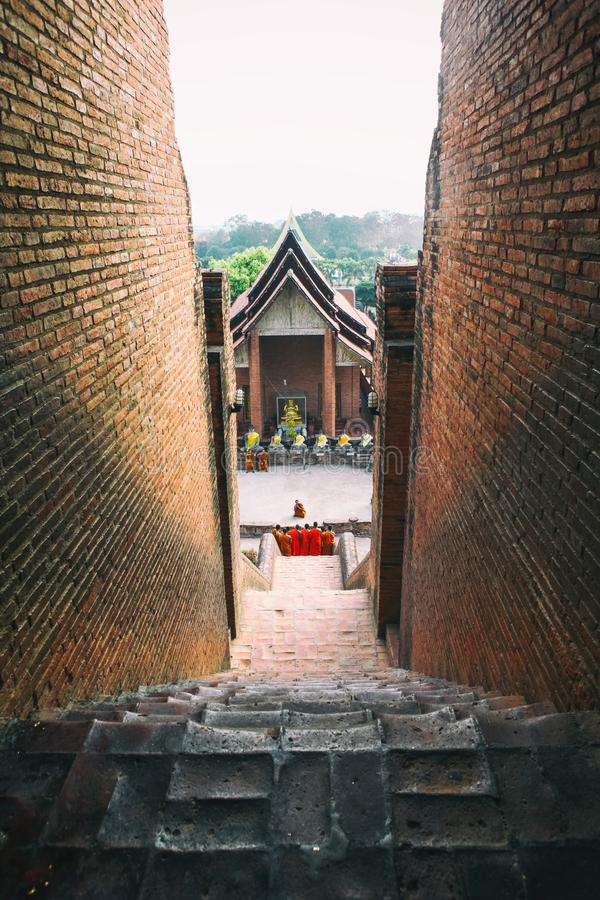 Monks walk down from the stairs of Wat Yai Chaimongkhon royalty free stock photo