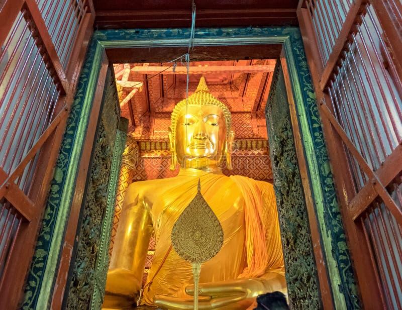 Ayutthaya, Tailândia - 9 de maio de 2015: Elegante dourado da estátua grande de buddha na capela no templo phanan do choeng do wa fotografia de stock