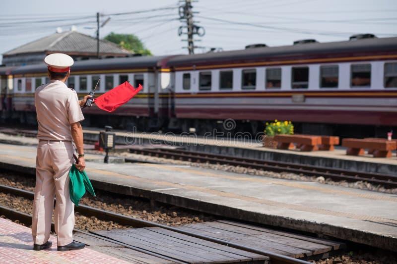Ayutthaya, Tailandia 1° novembre 2017: Il personale del treno fa un segnale con la bandiera rossa alla gente che il treno arriva immagini stock