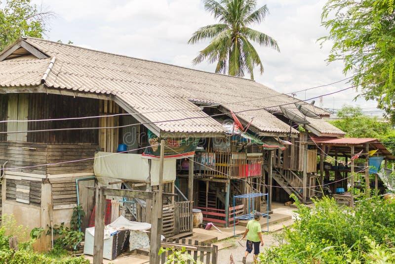 Ayutthaya Thailand - alte Frauen, die um ihr Holzhaus gehen stockbilder