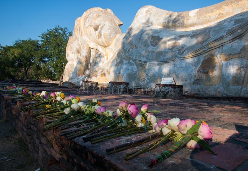 Ayutthaya Thailand 2018 : Big reclining buddha statue at Wat Lokayasutharam or Wat pranon temple . many oblation are flower lotus royalty free stock images