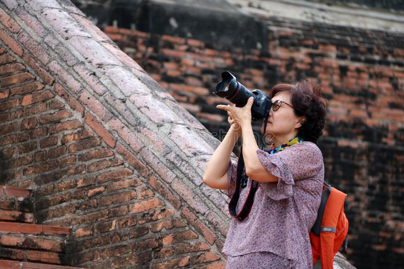 Women tourists taking pictures and background ancient brick at Yai Chaimongkol Temple, Thailand royalty free stock images
