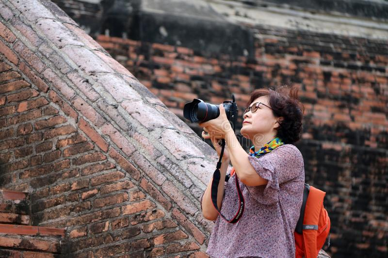 Women tourists taking pictures and background ancient brick at Yai Chaimongkol Temple, Thailand. Ayutthaya, Thailand - Oct 9, 2018 : Women tourists taking stock image