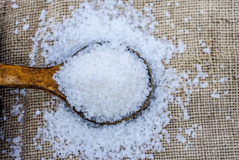 Azúcar blanco en cucharada de madera El azúcar es el nombre genérico para el dulce, soluble imagen de archivo libre de regalías