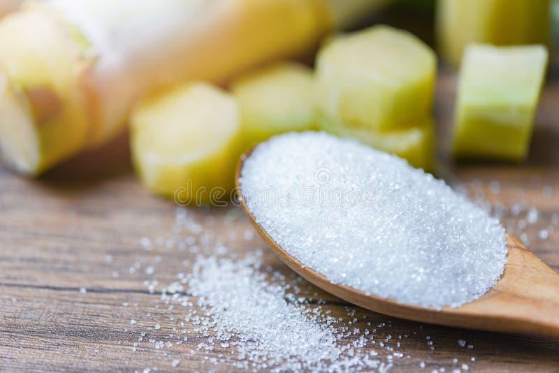 Azúcar blanco en fondo de madera de madera de la tabla de la caña de azúcar de la cuchara y foto de archivo