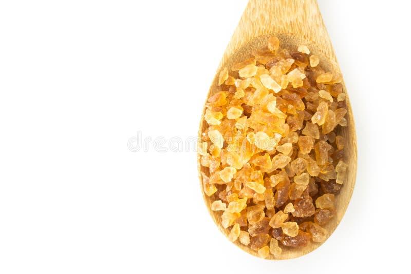 Azúcar de caña de Brown de la opinión superior del primer en cuchara de madera en el backg blanco fotografía de archivo