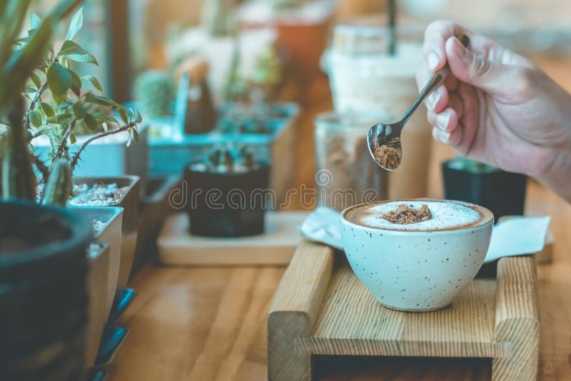Az?car de colada de la mujer en una taza blanca de coffe fotos de archivo