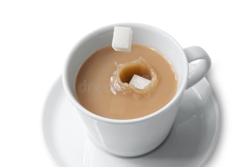 Azúcar de cubo que cae en la taza de té fotografía de archivo