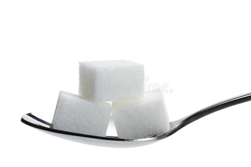 Azúcar de terrón tres en una cuchara imagenes de archivo