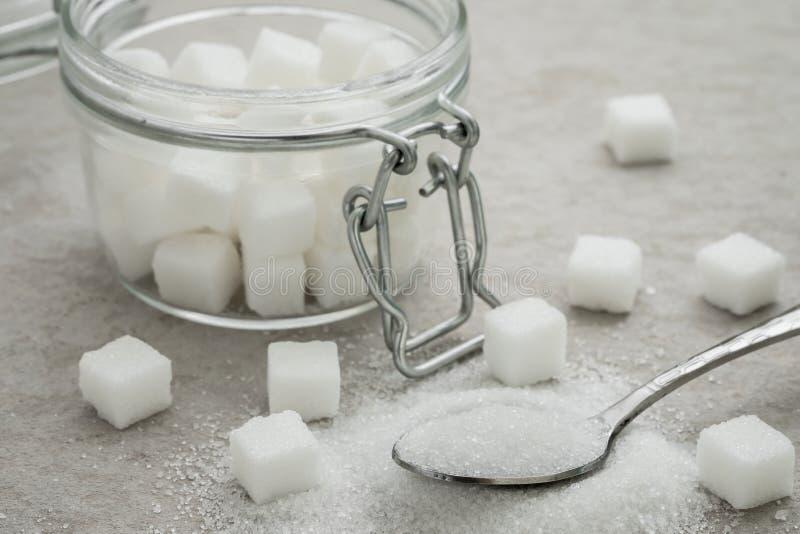 Azúcar en el tarro de la cuchara y del vidrio imagen de archivo