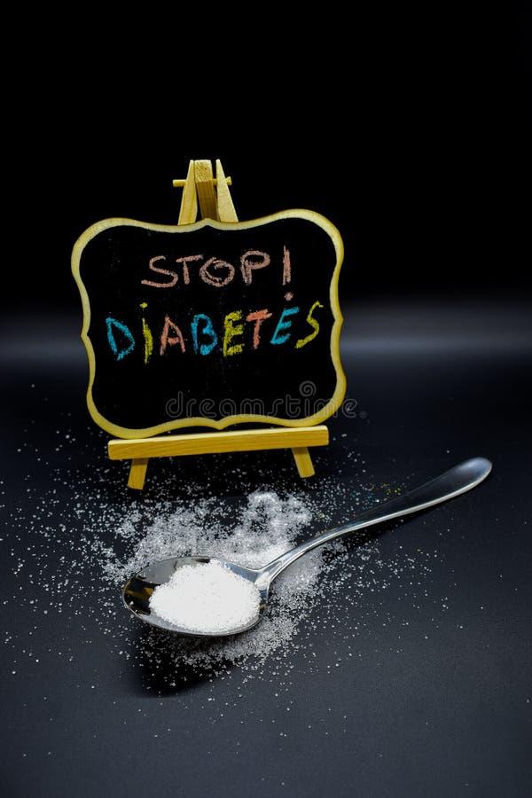 Azúcar en una cuchara con un mensaje de la diabetes de la parada en una pizarra fotografía de archivo libre de regalías