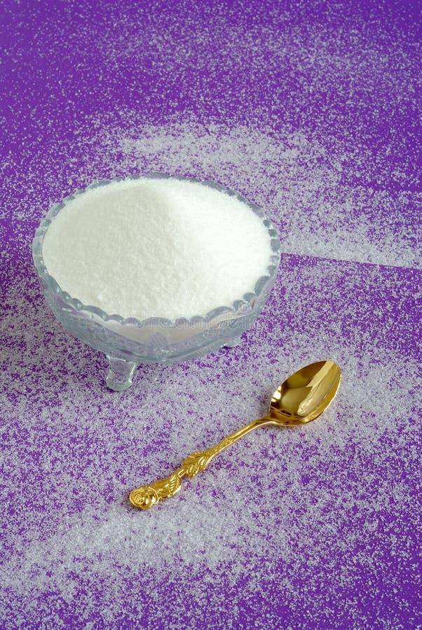Azúcar granulado blanco puro en un fondo púrpura fotografía de archivo libre de regalías
