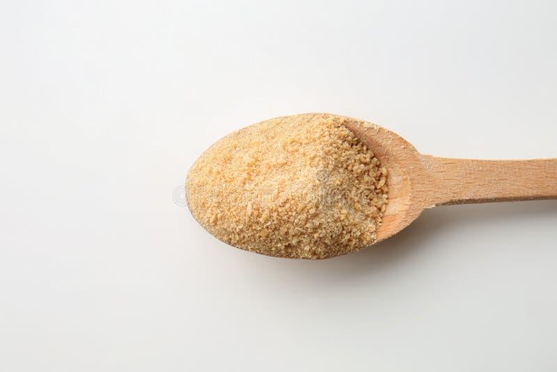 Azúcar marrón granulado en cuchara de madera en el fondo blanco imagen de archivo