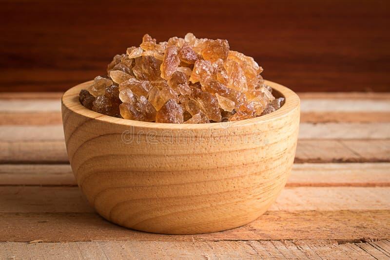 Azúcar natural de la roca en cuenco de madera en la tabla rústica fotos de archivo