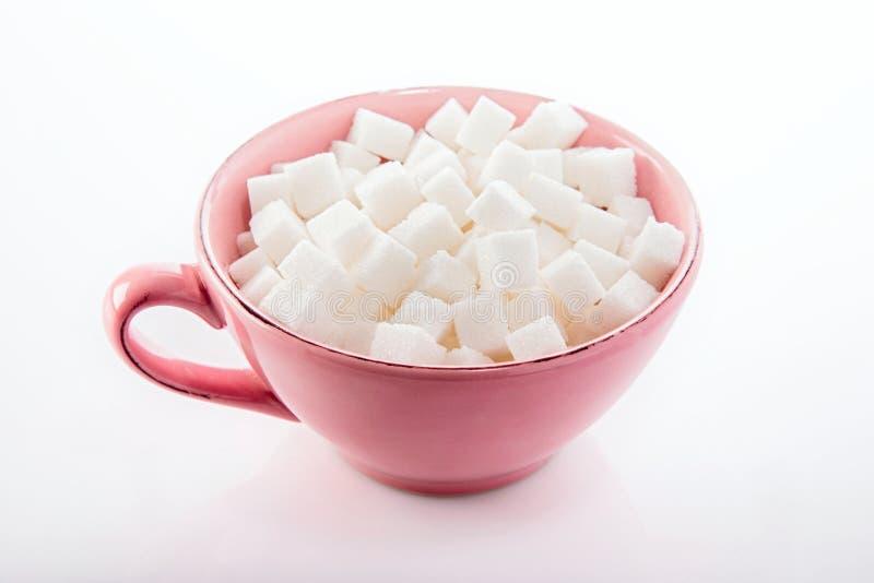 Azúcar refinado en una taza imagen de archivo