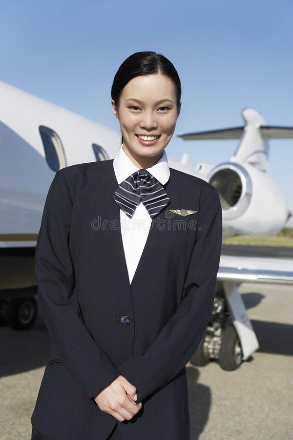 Azafata bonita joven Standing At Airfield imagen de archivo
