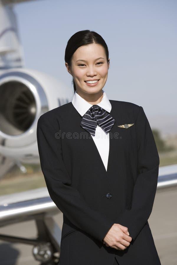 Azafata bonita joven Standing At Airfield fotos de archivo