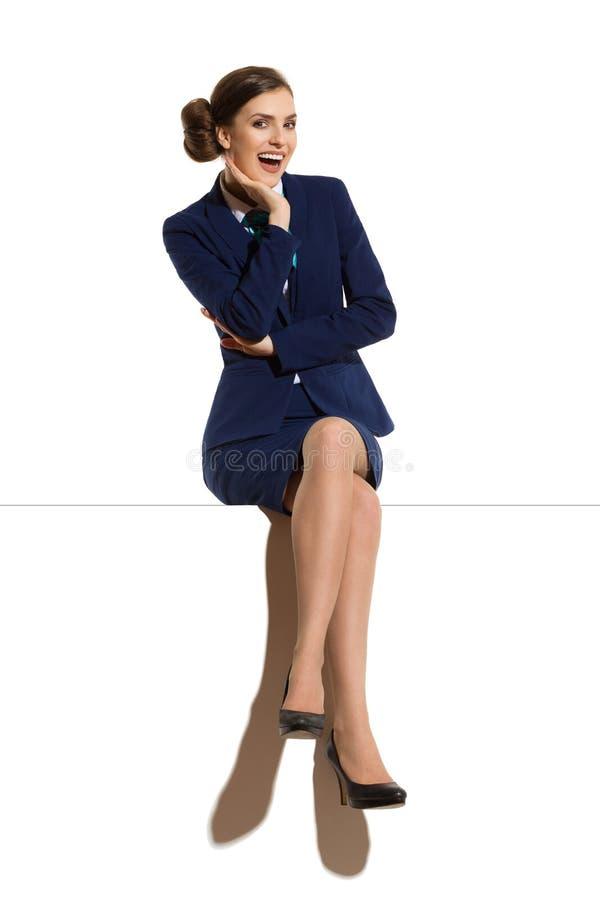 Azafata de risa Is Sitting On al top con las piernas cruzadas fotografía de archivo