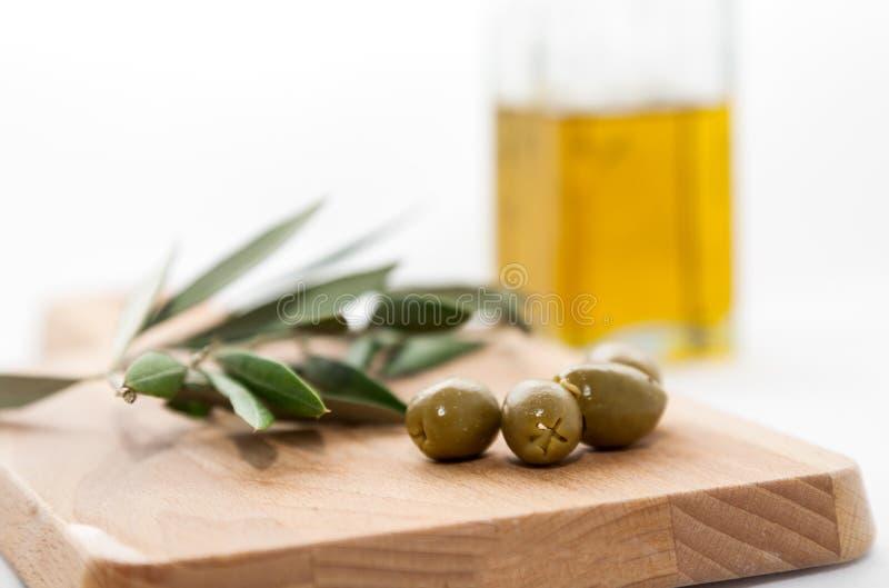 Azeite com as azeitonas isoladas no fundo branco imagem de stock