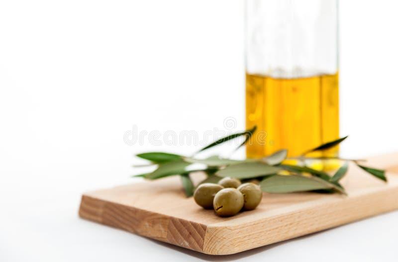 Azeite com as azeitonas isoladas no fundo branco fotografia de stock