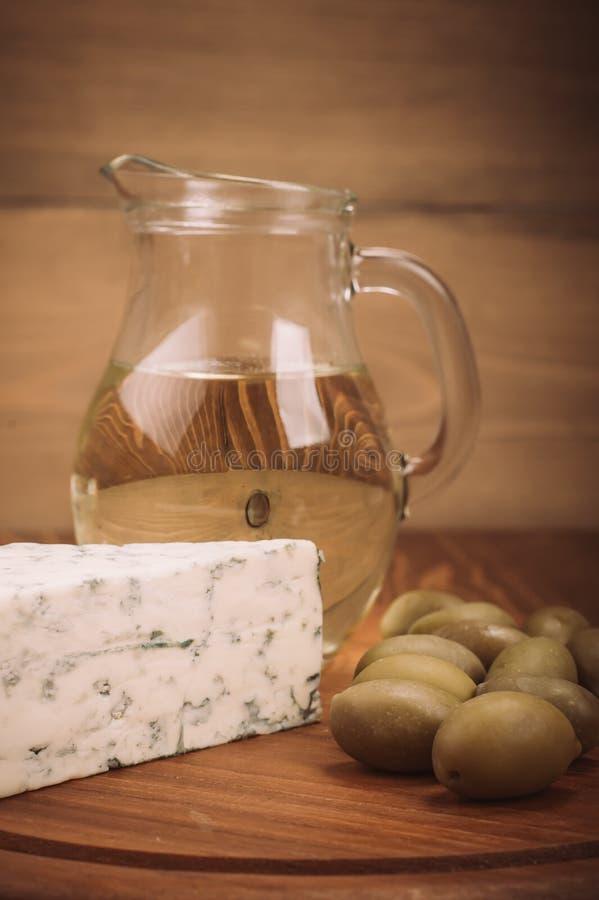 Azeite com queijo azul e azeitonas na placa de madeira imagem de stock royalty free