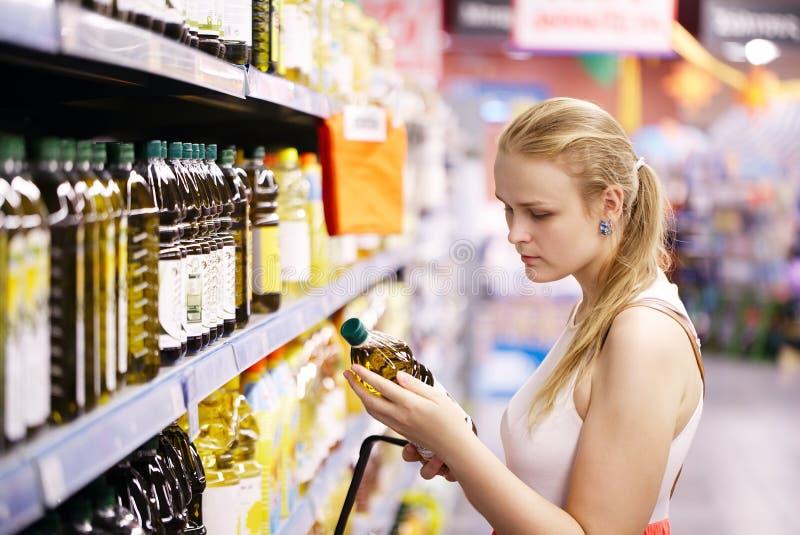 Azeite de compra da jovem mulher fotografia de stock
