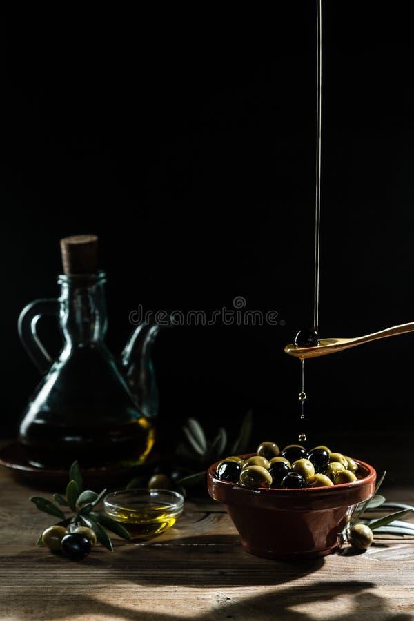 Azeite e ramo de oliveira na tabela de madeira fotos de stock royalty free