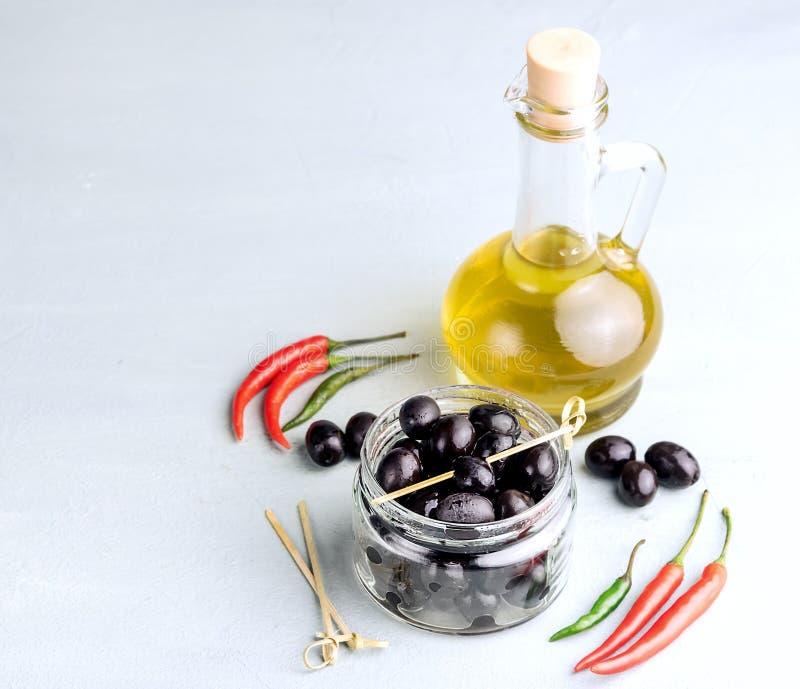 Azeite em umas garrafas com copyspace das azeitonas pretas e das folhas no fundo imagem de stock