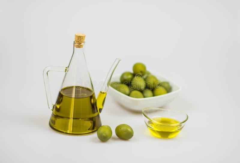 Azeite italiano com azeitonas verdes no fundo do whithe imagem de stock