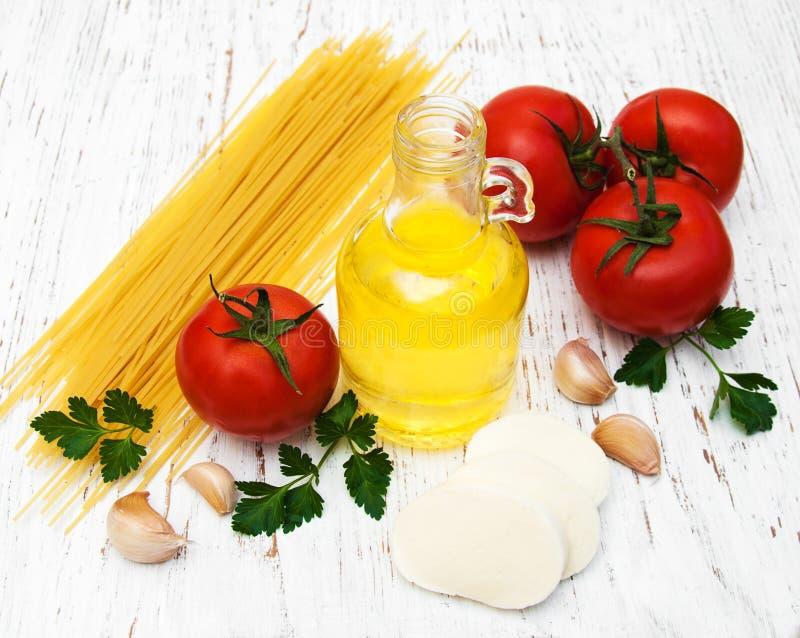 Azeite, mozzarella, espaguetes, alho e tomates foto de stock