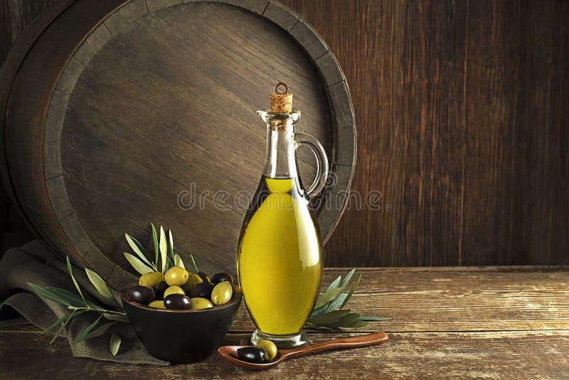 Azeite na garrafa com azeitonas e ramo imagens de stock