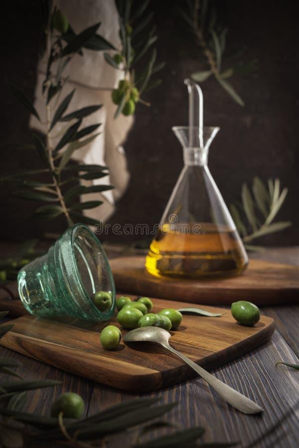 Azeite virgem extra na garrafa de vidro com o copo lançado das azeitonas no fundo rústico Baixa chave imagens de stock