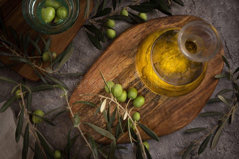 Azeite virgem extra na garrafa de vidro com ramo das azeitonas no fundo rústico Baixa chave imagens de stock