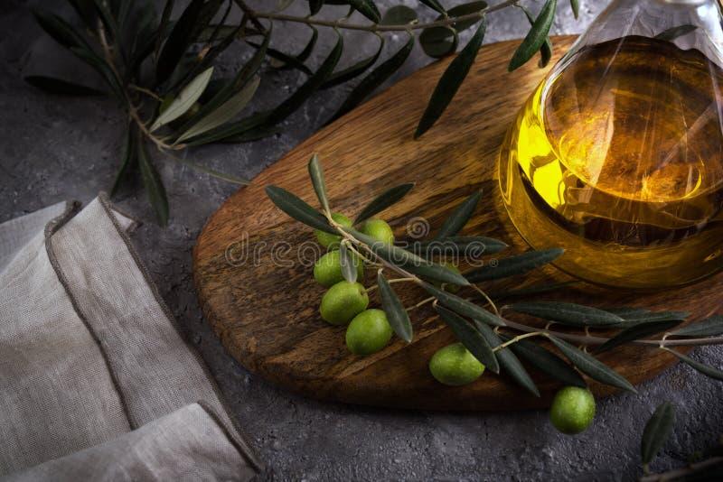 Azeite virgem extra na garrafa de vidro com ramo das azeitonas no fundo rústico Baixa chave imagem de stock royalty free