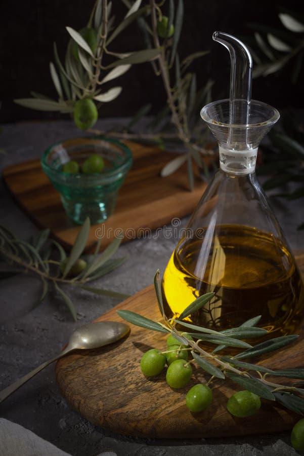 Azeite virgem extra na garrafa de vidro com ramo das azeitonas no fundo rústico Baixa chave foto de stock royalty free