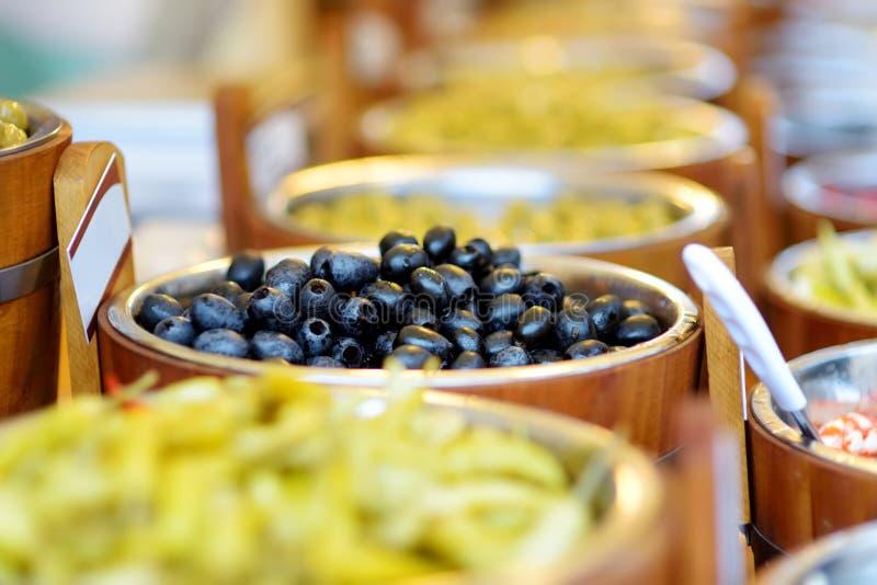 Azeitona picada orgânica, alho, pimentos quentes, capers e tomatos secos por sol, comercializados em Vilnius, Lituânia fotografia de stock royalty free